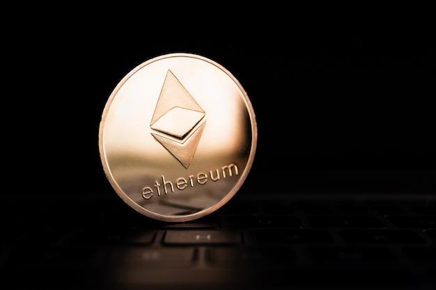 Eine goldene münze mit ethereum-symbol auf computertastatur.
