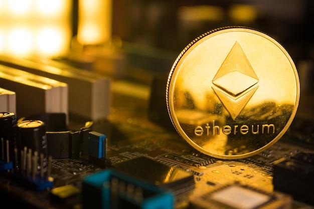 Eine goldene münze mit ethereum-symbol auf einem mainboard.