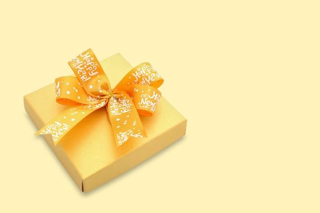 Eine goldfarbene geschenkbox mit einem leuchtend gelben band auf gelbem hintergrund