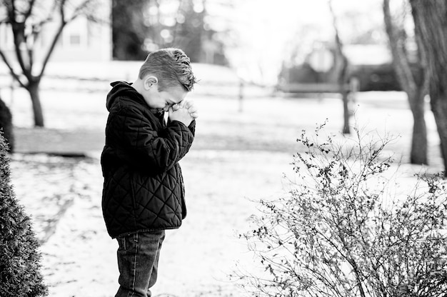 Eine graustufenaufnahme eines betenden kindes