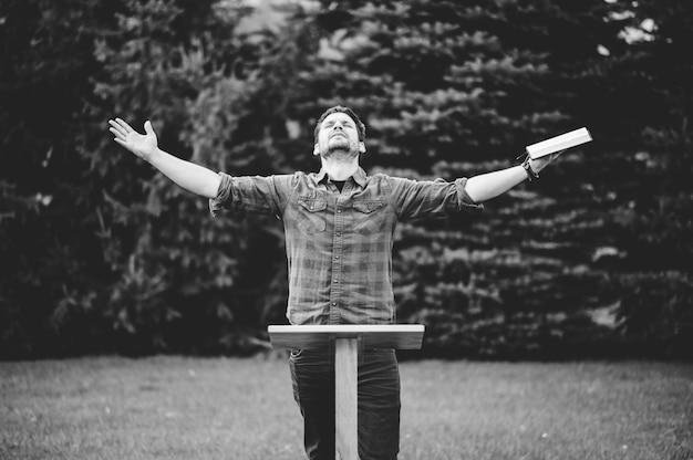 Eine graustufenaufnahme eines christlichen mannes, der beim beten die bibel hält