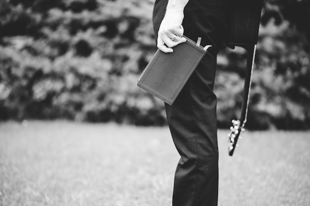 Eine graustufenaufnahme eines mannes, der die bibel und eine gitarre auf dem rücken hält
