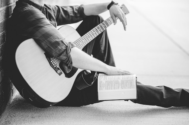 Eine graustufenaufnahme eines mannes mit gitarre und aufgeschlagener bibel