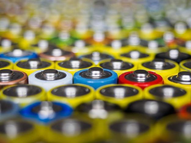 Eine große anzahl alter aa-batterien in verschiedenen farben.