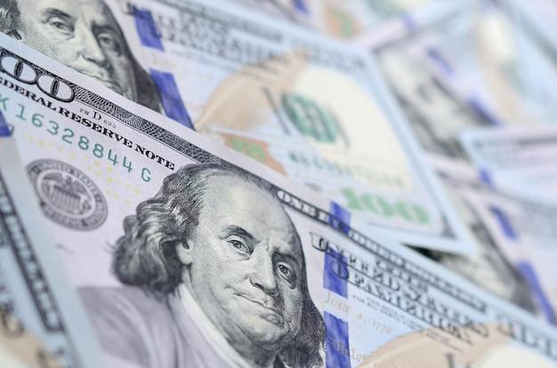 Eine große anzahl von us-dollar-scheinen eines neuen designs mit einem blauen streifen in der mitte. ansicht von oben