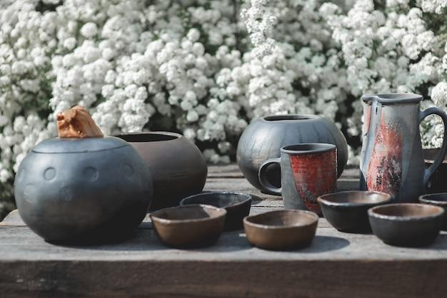 Eine große auswahl an schwarzer keramik aus ton auf weißem blumenhintergrund