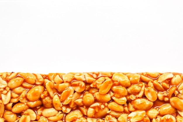 Eine große fliese des gebratenen erdnussriegels in einer süßen melasse. kozinaki nützliche und leckere süßigkeiten aus dem osten