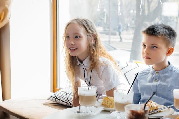 Eine große, freundliche gesellschaft von kindern feiert den urlaub in einem café mit einem köstlichen dessert. der tag der geburt.