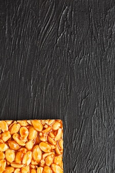 Eine große goldene fliese mit erdnüssen, eine tafel mit süßer melasse. kozinaki nützliche und leckere süßigkeiten aus dem osten