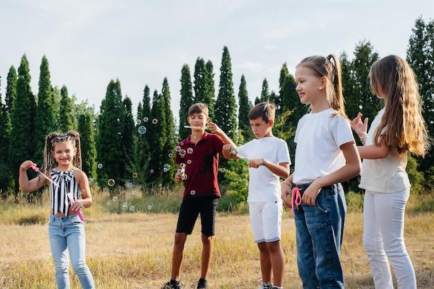 Eine große gruppe fröhlicher kinder spielt im park und bläst seifenblasen auf. spiele im kinderlager.
