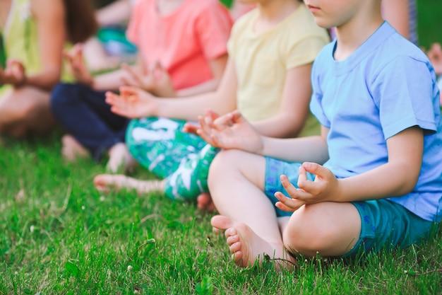 Eine große gruppe kinder nahm an yoga im park teil, der auf dem gras sitzt.