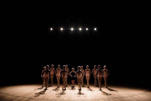 Eine große gruppe von kindern probt und tanzt das ballett.
