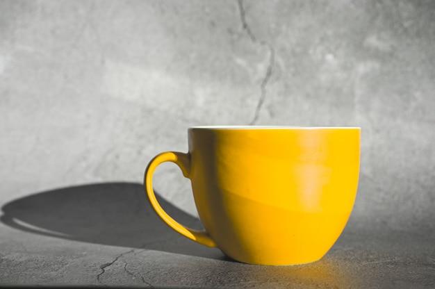 Eine große kaffeetasse und schatten auf betonoberfläche