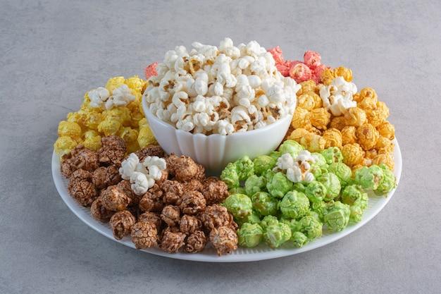Eine große platte mit beschichteten popcorn-bonbons mit einer schüssel popcorn in der mitte auf marmor.