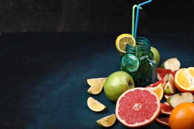 Eine große scheibe grapefruit, eine scheibe obst und ein glas mojito.
