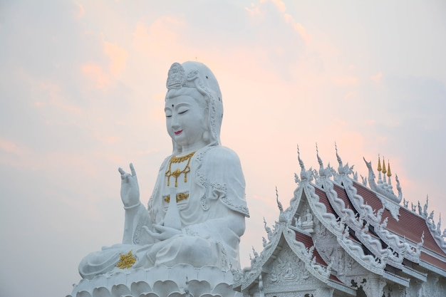 Eine große schöne weiße antike guan yin-statue ist gepaart mit einem schönen tempel oder gegenüber