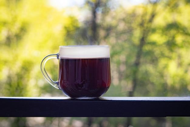 Eine große transparente tasse mit schwarzem kaffee steht auf einem dunklen eisentisch vor einem unscharfen hintergrund sommergrüner bäume. guten morgen konzept. frische ideen. weicher fokus.