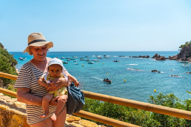 Eine großmutter und ein enkel haben spaß im sommer in cala canyet neben der stadt tossa de mar. girona, costa brava im mittelmeer