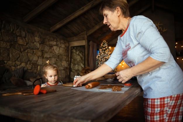 Eine großmutter und ihre reizende blonde enkelin kochen plätzchen zusammen in einem haus, das für weihnachten verziert wird