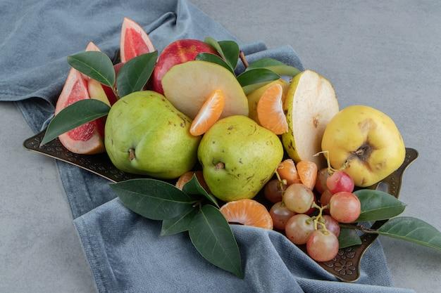 Eine großzügige portion verschiedener früchte auf einem tablett aus marmor