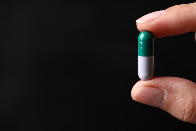 Eine grün-graue medizinische pille in der hand halten.