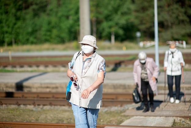 Eine gruppe älterer älterer reisender mit masken im gesicht überquert die eisenbahnschienen