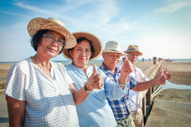 Eine gruppe älterer freunde trifft sich, um sich am meer zu entspannen. sie sind gesund und glücklich. daumen hoch