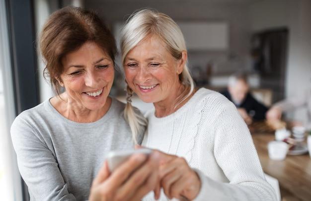 Eine gruppe älterer freunde zu hause mit smartphone.