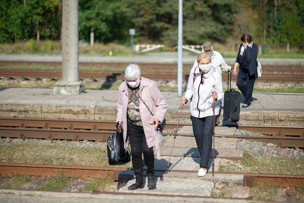Eine gruppe älterer reisender mit masken im gesicht überquert die eisenbahnschienen