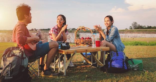 Eine gruppe asiatischer freunde, die ukelele spielen und in den sommerferien ein picknick machen. sie sind glücklich und haben spaß an den feiertagen.