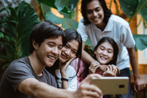 Eine gruppe asiatischer freunde tätigt videoanrufe mit einem smartphone im garten, während sie auf einer bank sitzen