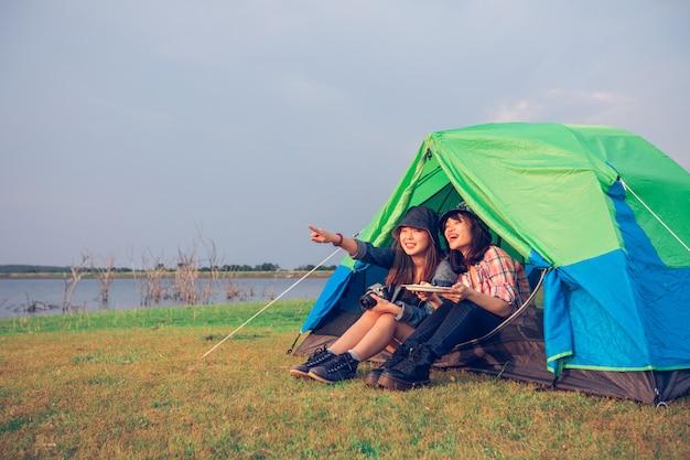 Eine gruppe asiatischer freundtourist, die zusammen mit glück im sommer beim haben des kampierens trinkt