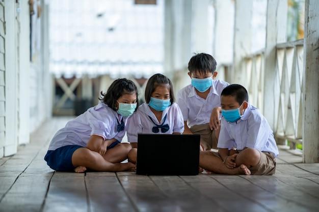 Eine gruppe asiatischer grundschüler, die eine hygienemaske tragen, um den ausbruch von covid 19 während des schulanfangs zu verhindern, eröffnet ihre schule wieder.