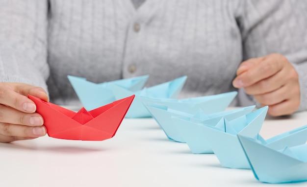 Eine gruppe blauer papierboote folgt einem res-boot vor einem weißen tisch. das konzept eines starken und charismatischen führers in einem team, der die massen manipuliert