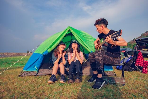 Eine gruppe des asiatischen freundtouristen, der gitarre zusammen mit glück im sommer beim haben des kampierens nahe see bei sonnenuntergang trinkt und spielt