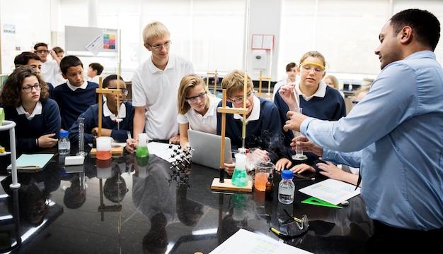 Eine gruppe des studenten, der über ein wissenschaftsexperiment hört