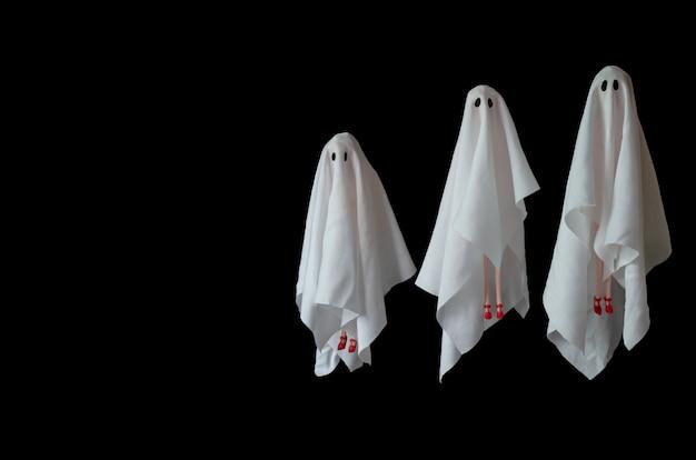 Eine gruppe des weißen blattkostüms des weiblichen geistes, das in die luft mit schwarzem hintergrund fliegt. minimales halloween unheimlich.