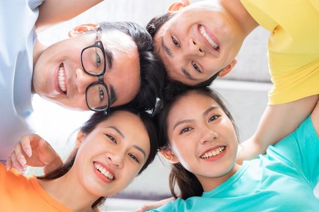 Eine gruppe enger asiatischer freunde, die ihre arme umeinander legen, um teamwork zu zeigen