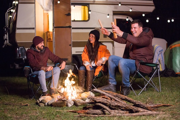 Eine gruppe enger freunde, die sich am lagerfeuer aufwärmen und zusammen lachen. retro-wohnmobil.