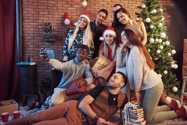 Eine gruppe fröhlicher alter freunde kommuniziert miteinander und macht ein selfie-foto. das neue jahr kommt. feiern sie das neue jahr in gemütlicher atmosphäre
