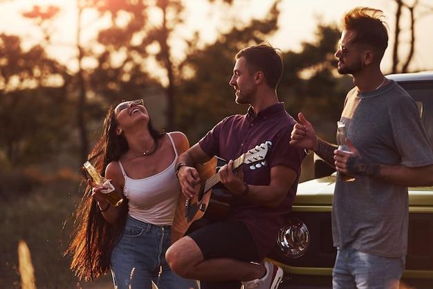 Eine gruppe fröhlicher freunde hat ein schönes wochenende an einem sonnigen tag in der nähe ihres grünen autos im freien