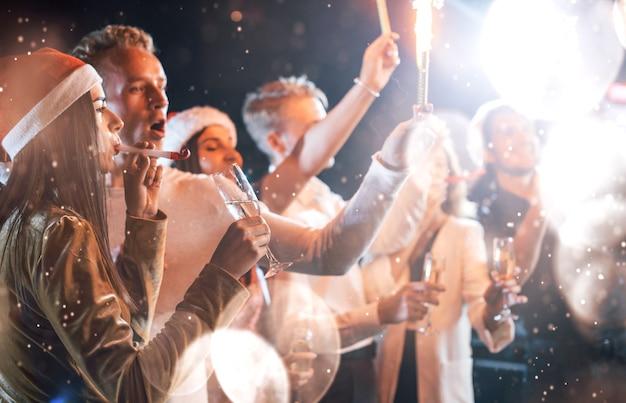 Eine gruppe fröhlicher junger leute feiert drinnen party und feiert neues jahr.