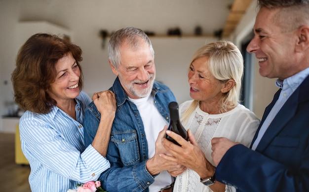 Eine gruppe fröhlicher seniorenfreunde bei der dinnerparty zu hause, gruß.