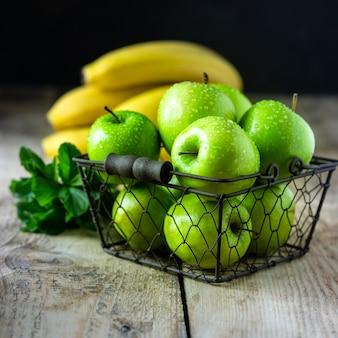 Eine gruppe gesunder grüner äpfel, bananen und minze sind zutaten für einen smoothie. entgiftung, diät, gesundes, vegetarisches lebensmittelkonzept.