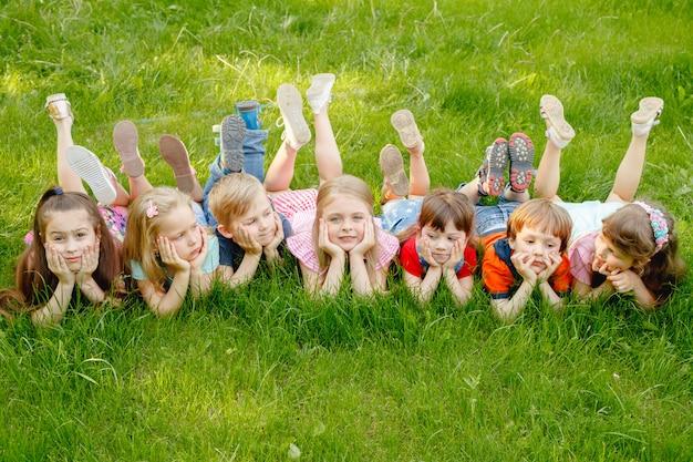Eine gruppe glückliche kinder von jungen und von mädchen laufen in den park auf dem gras an einem sonnigen sommertag