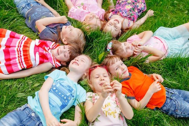 Eine gruppe glückliche kinder von jungen und von mädchen laufen in den park auf dem gras an einem sonnigen sommertag.