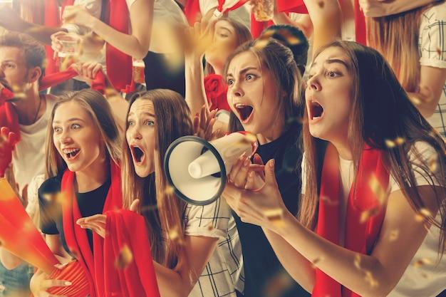 Eine gruppe glücklicher fans jubelt um ihren mannschaftssieg.