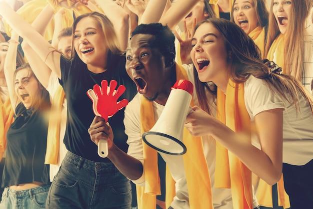 Eine gruppe glücklicher fans jubelt um ihren mannschaftssieg