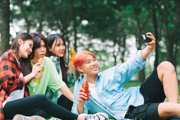 Eine gruppe glücklicher junger asiaten macht fotos beim gemeinsamen check-in im park