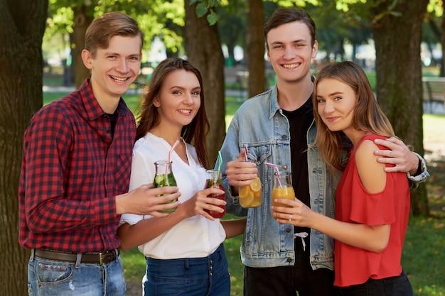 Eine gruppe glücklicher junger leute genießt detox-cocktails und verbringt im sommer zeit miteinander. freundschaft, jugendlicher lebensstil, vegetarische ernährung, fitnessessen für unterwegs, erfolgreiches gewichtsverlustkonzept loss
